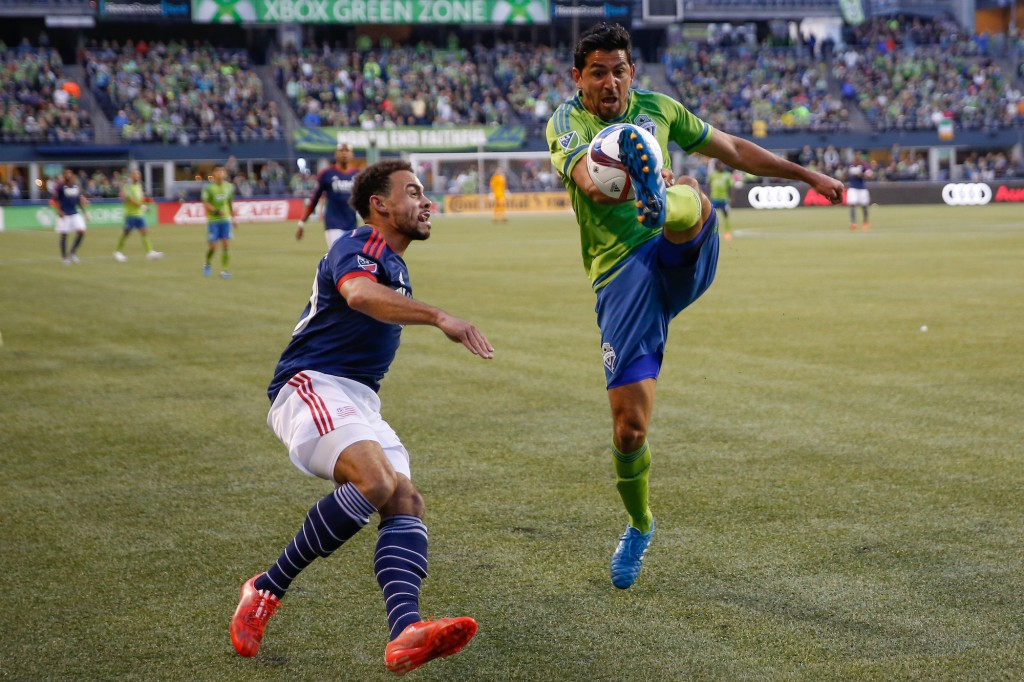 SEATTLE, WA - MARCH 08: Leonardo Gonzalez #12 of the Seattle Sounders FC battles Kevin Alston #30 of the New England Revolution at CenturyLink Field on March 8, 2015 in Seattle, Washington. The Sounders defeated the Revolution 3-0. (Photo by Otto Greule Jr/Getty Images)