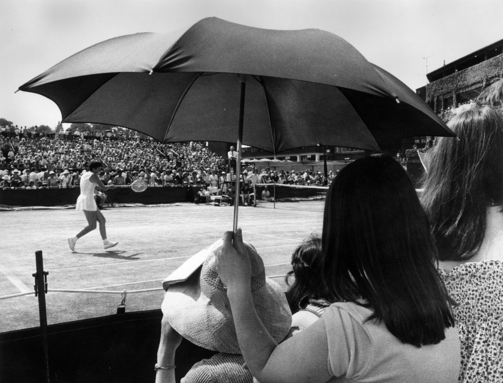 25th June 1976: A spectator at the Wimbledon Lawn Tennis Championships using an umbrella to shelter from the sun, as Marise Kruger of South Africa plays a match. (Photo by Roger Jackson/Central Press/Getty Images)