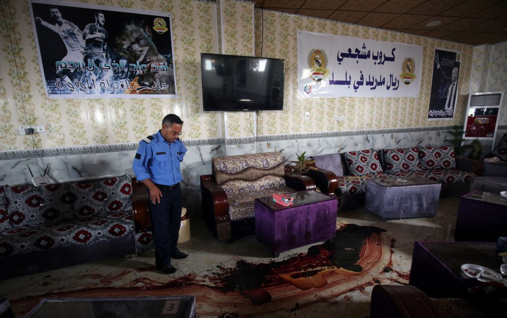 An Iraqi policeman stands over a trail of blood and debris at a cafe, that was popular with local fans of Spain's Real Madrid football club, in the Balad area, north of the capital Baghdad, on May 14, 2016, a day after a deadly raid claimed by Islamic State group militants. At least 16 people were killed and 30 wounded, including several members of the security forces, in the attack in the town of Balad and the ensuing chase, officials said. / AFP / AHMAD AL-RUBAYE (Photo credit should read AHMAD AL-RUBAYE/AFP/Getty Images)