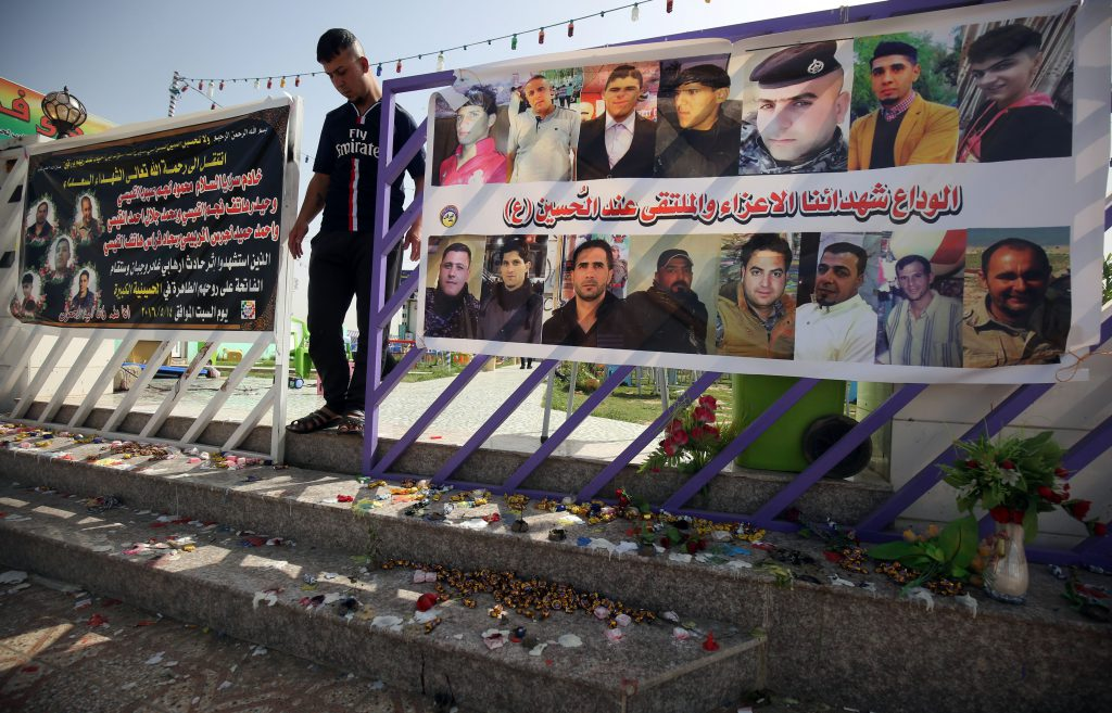 An Iraqi man walks past a poster bearing the portraits of the victims at a cafe, that was popular with local fans of Spain's Real Madrid football club, in the Balad area, north of the capital Baghdad, on May 14, 2016, a day after a deadly raid claimed by Islamic State group militants. At least 16 people were killed and 30 wounded, including several members of the security forces, in the attack in the town of Balad and the ensuing chase, officials said. / AFP / AHMAD AL-RUBAYE (Photo credit should read AHMAD AL-RUBAYE/AFP/Getty Images)