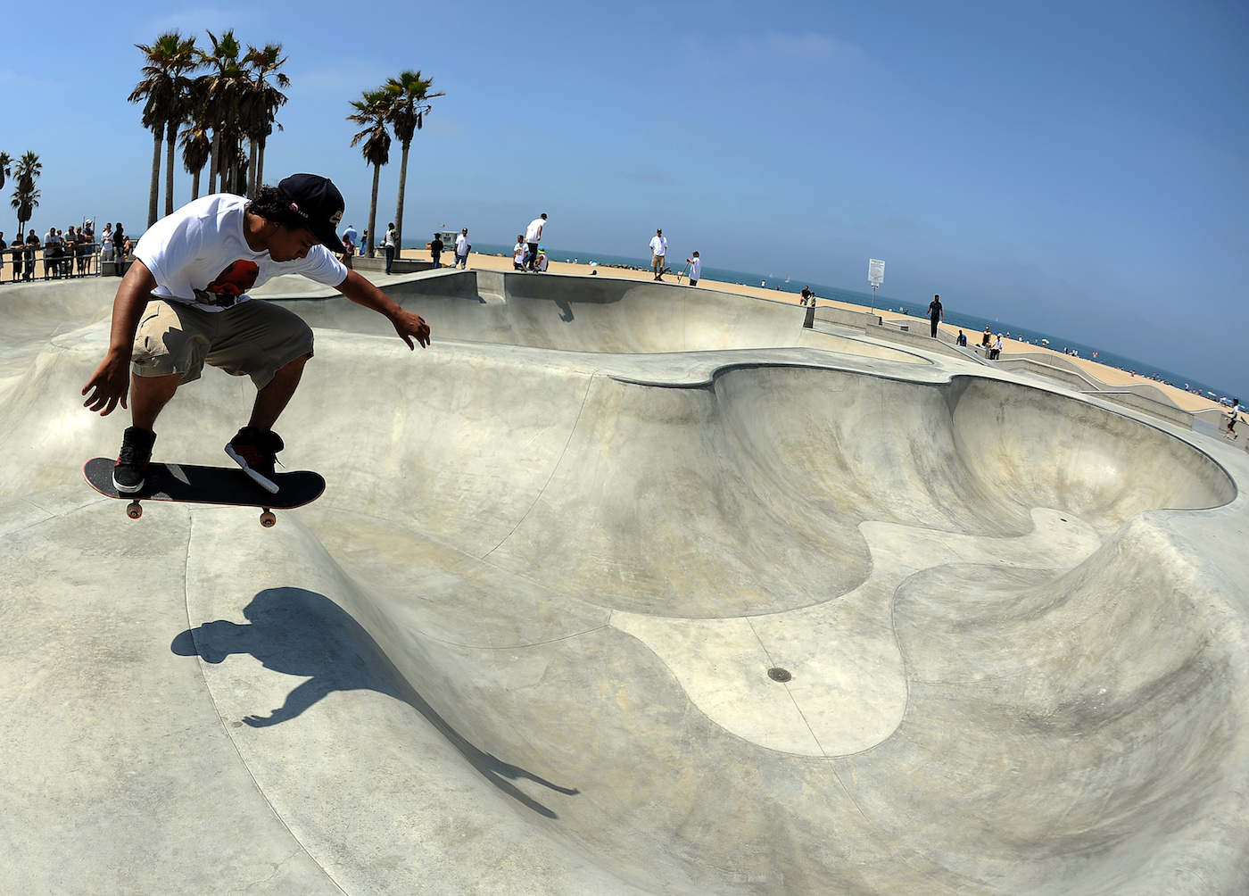 "A young man jumps with his skateboard at Venice Beach Skateboard Park on July 4, 2011 in Venice, California. The first skateboards to reach public notice came out of the surfing craze of the early 1960s, developed to help surfers practice when waves were unfavorable. The first prototypes were simple wooden boards with roller-skate wheels attached, and the practice was sometimes referred to as ""sidewalk surfing."" The surfing group Jan and Dean even had a minor hit called ""Sidewalk Surfing"" in 1964. By the mid-1980s skateboards were mass produced and sold throughout the United States. AFP PHOTO / GABRIEL BOUYS (Photo credit should read GABRIEL BOUYS/AFP/Getty Images)"