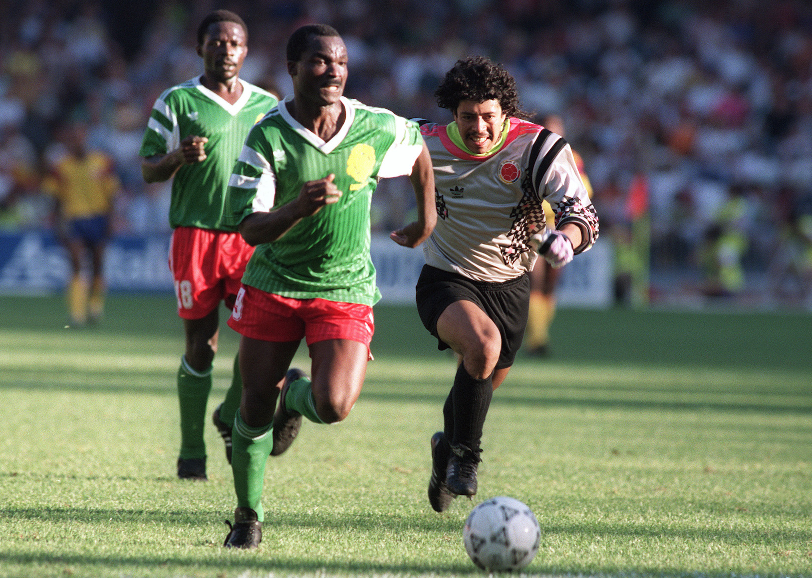 NAPLES, ITALY - JUNE 23: Forward Roger Milla from Cameroon runs past Colombian goalkeeper Jose Higuita (R) after stealing the ball from him on his way to score a goal 23 June 1990 in Naples during the World Cup second round soccer match between Cameroon and Colombia. Milla scored two goals in extra time to help Cameroon defeat Colombia 2-1 (0-0 at the end of regulation time) (Photo credit should read STAFF/AFP/Getty Images)