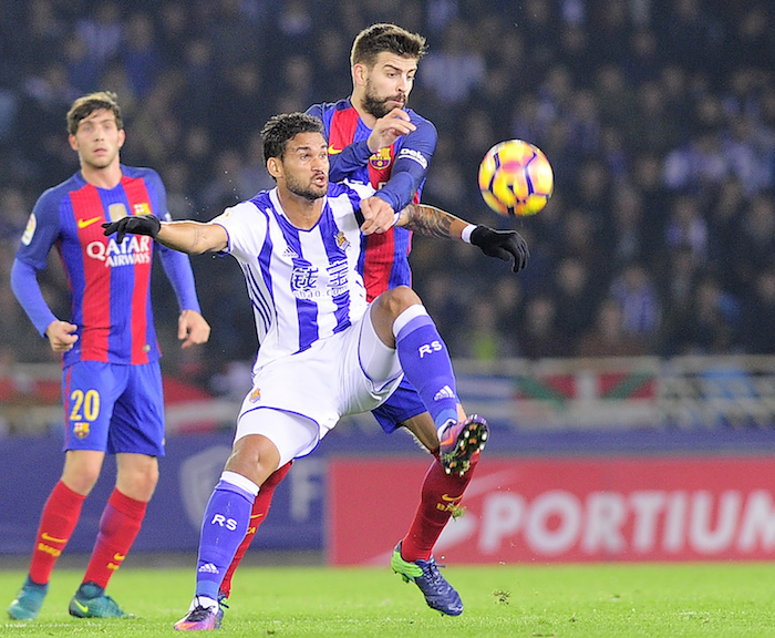 Real Sociedad's Brazilian forward Willian Jose (L) vies with Barcelona's defender Gerard Pique (R) during the Spanish league football match Real Sociedad vs FC Barcelona at the Anoeta stadium in San Sebastian, on November 27, 2016. / AFP / ANDER GILLENEA (Photo credit should read ANDER GILLENEA/AFP/Getty Images)