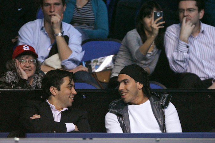 Manchester City's Argentinian footballer Carlos Tevez (Front R) speaks with football agent Kia Joorabchian, as they watch Juan Martin Del Potro of Argentina play against Roger Federer of Switzerland in a Singles match during the Barclays ATP World Tour Tennis Finals in London, on November 26, 2009. AFP PHOTO/GLYN KIRK (Photo credit should read GLYN KIRK/AFP/Getty Images)