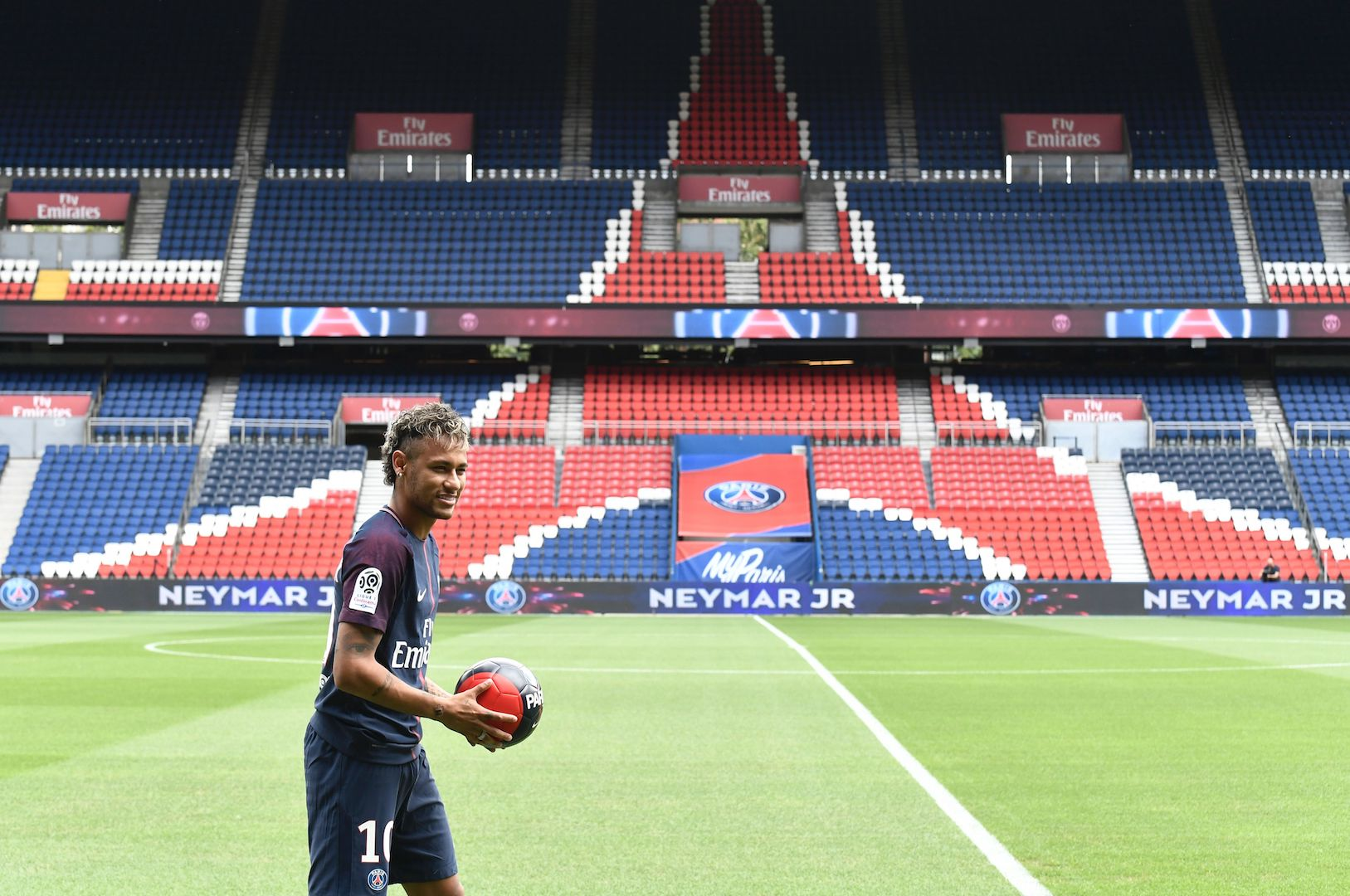"Brazilian superstar Neymar poses with a ball during his official presentation at the Parc des Princes stadium on August 4, 2017 in Paris after agreeing a five-year contract following his world record 222 million euro ($260 million) transfer from Barcelona to Paris Saint Germain's (PSG). Paris Saint-Germain have signed Brazilian forward Neymar from Barcelona for a world-record transfer fee of 222 million euros (around $264 million), more than doubling the previous record. Neymar said he came to Paris Saint-Germain for a ""bigger challenge"" in his first public comments since arriving in the French capital. / AFP PHOTO / PHILIPPE LOPEZ (Photo credit should read PHILIPPE LOPEZ/AFP/Getty Images)"