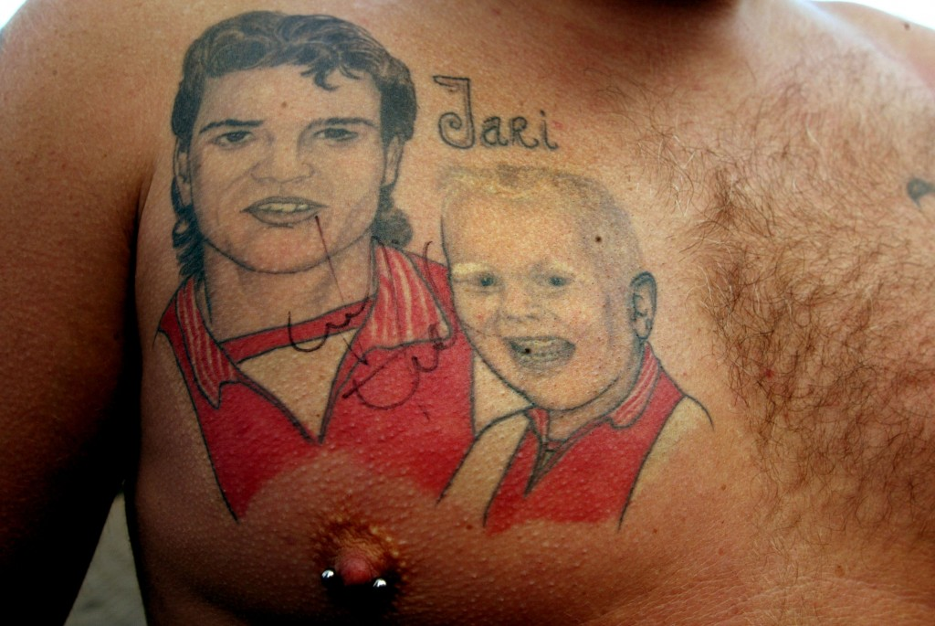 AMSTERDAM, NETHERLANDS - SEPTEMBER 9: Mike Weermeier displays a chest tattoo of Finnish soccer player Jari Litmanen (L) on the first day of practice where he starts for a second season with Ajax September 9, 2002 in Amsterdam, Netherlands. The child depicted to the left is Mike's eight-year-old son, Jari, who is named after idol Litmanen, who was transferred from Liverpool and is immensely popular in Holland. (Photo by Michel Porro/Getty Images)
