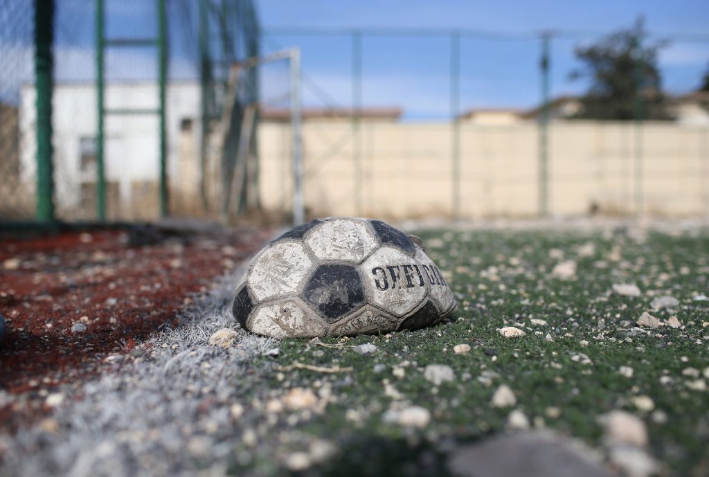 SINJAR, IRAQ - NOVEMBER 15: A deflated soccer ball lies next to a building hit by an airstrike on November 15, 2015 in Sinjar, Iraq. Kurdish forces, with the aid of massive U.S.-led coalition airstrikes, liberated Sinjar from ISIL extremists, known in Arabic as Daesh, in recent days. Local Yazidi fighters who fought with Kurdish forces have been taking any salvagable items out of the rubble, the town being uninhabitable and perilously close to the frontline. (Photo by John Moore/Getty Images)