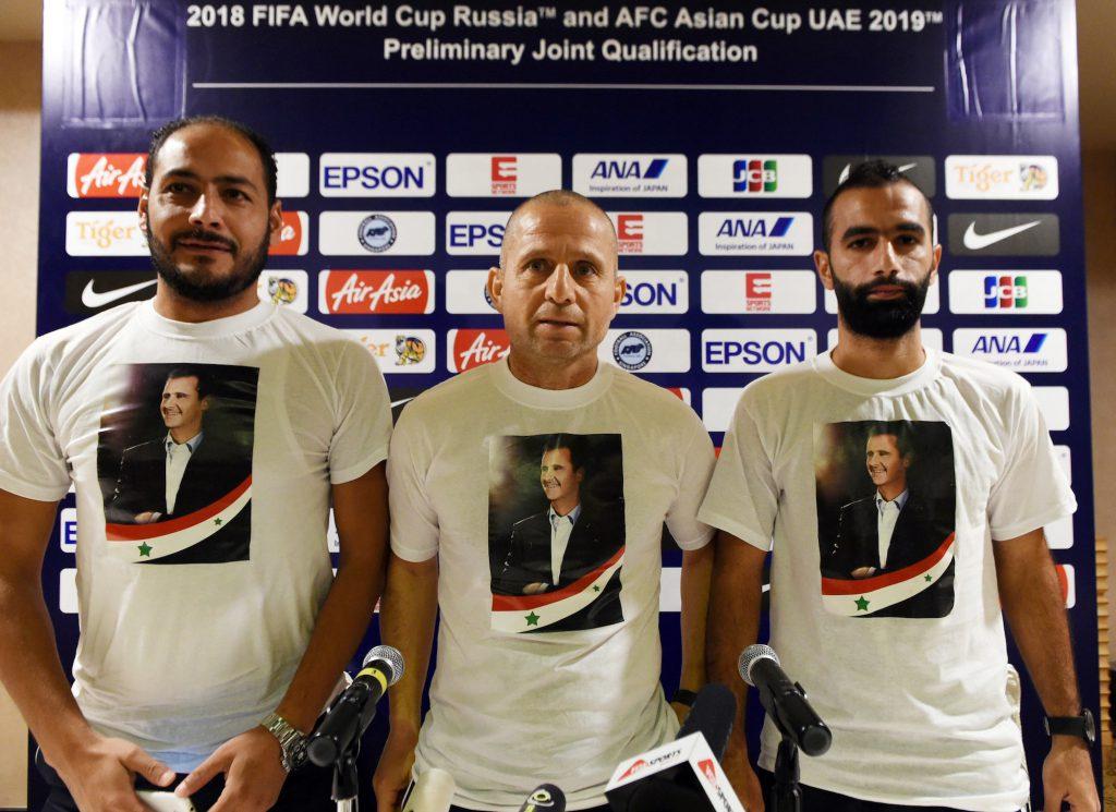 Il ct Fajr Ibrahim (C) e due giocatori con una t-shirt di Assad prima della partita di qualificazione contro Singapore, novembre 2016 (Roslan Rahman/Afp/Getty Images)