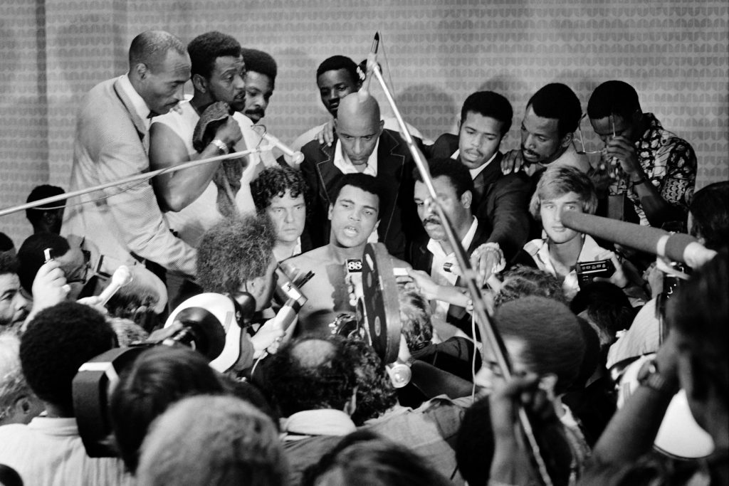 """TO GO WITH AFP STORIES In this photo taken on October 30, 1974 shows US boxing heavyweight champion Muhammad Ali (C) (born Cassius Clay) during a press conference after the heavyweight world championship in Kinshasa. On October 30, 1974 Muhammad Ali knocked out George Foreman in a clash of titans known as the """"Rumble in the Jungle"""", watched by 60 000 people in the stadium in Kinshasa and millions elsewhere AFP PHOTO (Photo credit should read STR/AFP/Getty Images)"""