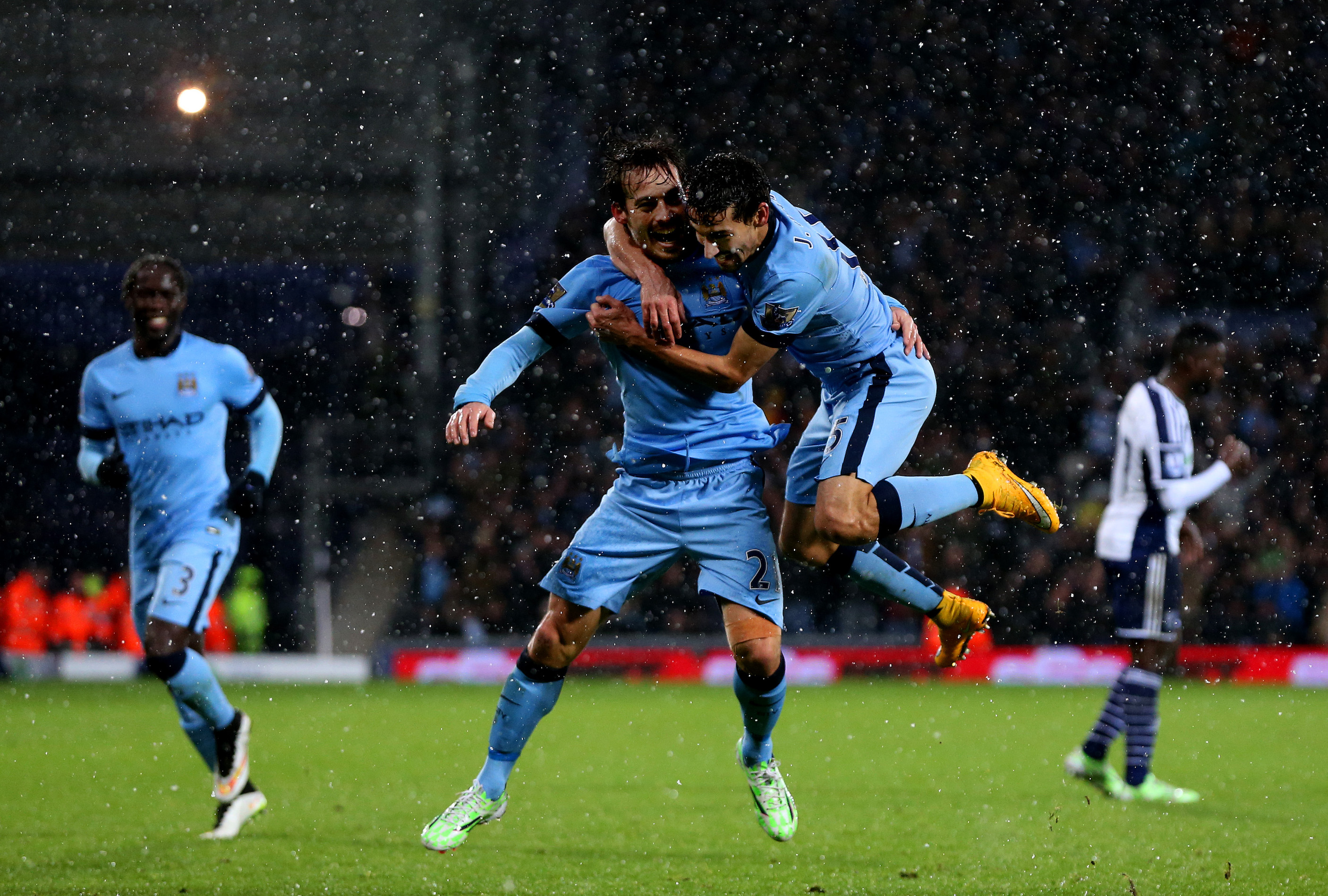 WEST BROMWICH, ENGLAND - DECEMBER 26: David Silva of Manchester City celebrates with team-mate Jesus Navas after scoring his team's third goal during the Barclays Premier League match between West Bromwich Albion and Manchester City at The Hawthorns on December 26, 2014 in West Bromwich, England. (Photo by Scott Heavey/Getty Images)
