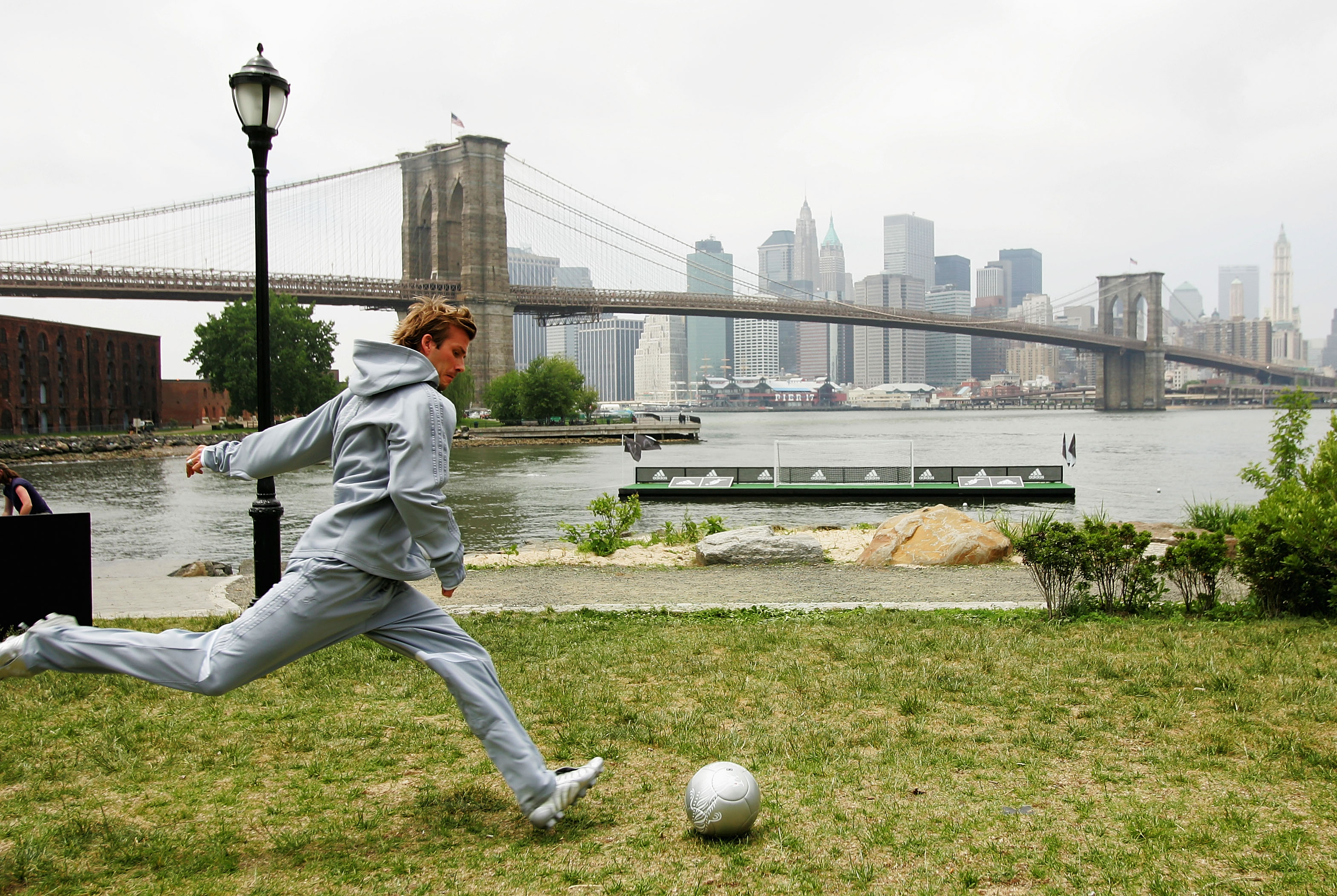 NEW YORK - JUNE 1: English soccer star David Beckham kicks soccer balls towards a goal set up on a raft in the East River, with the Brooklyn Bridge and the Manhattan skyline in the background on June 1, 2005 at the Brooklyn Bridge Park in the Brooklyn borough of New York City. (Photo by Ezra Shaw/Getty Images for adidas)