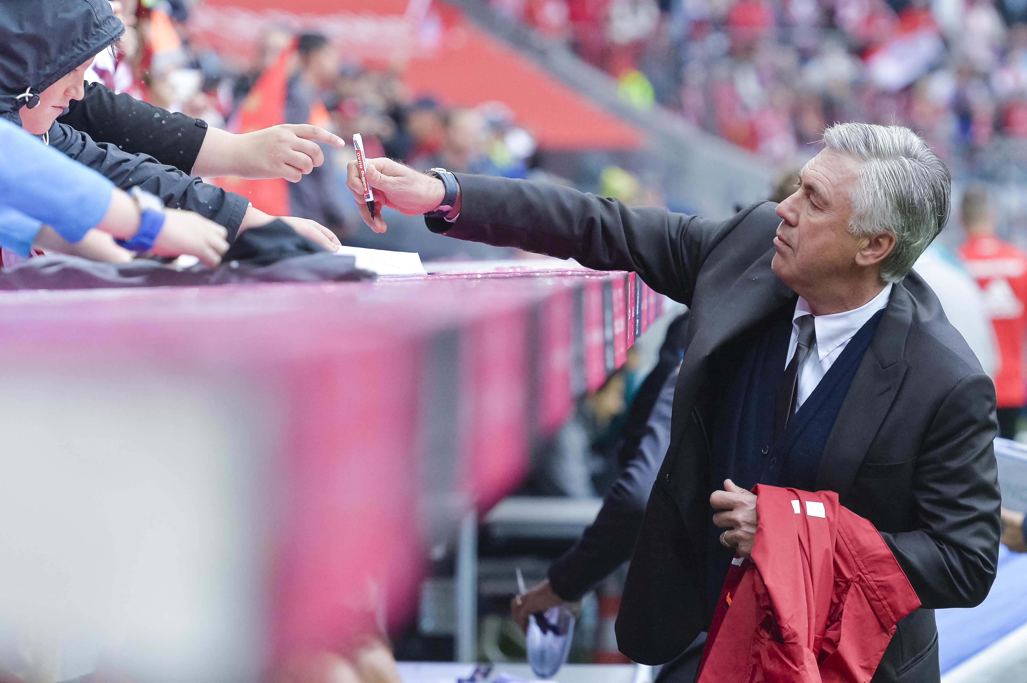 Bayern Munich's Italian head coach Carlo Ancelotti gives autographes during the German first division Bundesliga football match of Bayern Munich vs FC Ingolstadt in Munich, southern Germany, on September 17, 2016. / AFP / GUENTER SCHIFFMANN / RESTRICTIONS: DURING MATCH TIME: DFL RULES TO LIMIT THE ONLINE USAGE TO 15 PICTURES PER MATCH AND FORBID IMAGE SEQUENCES TO SIMULATE VIDEO. == RESTRICTED TO EDITORIAL USE == FOR FURTHER QUERIES PLEASE CONTACT DFL DIRECTLY AT + 49 69 650050 (Photo credit should read GUENTER SCHIFFMANN/AFP/Getty Images)