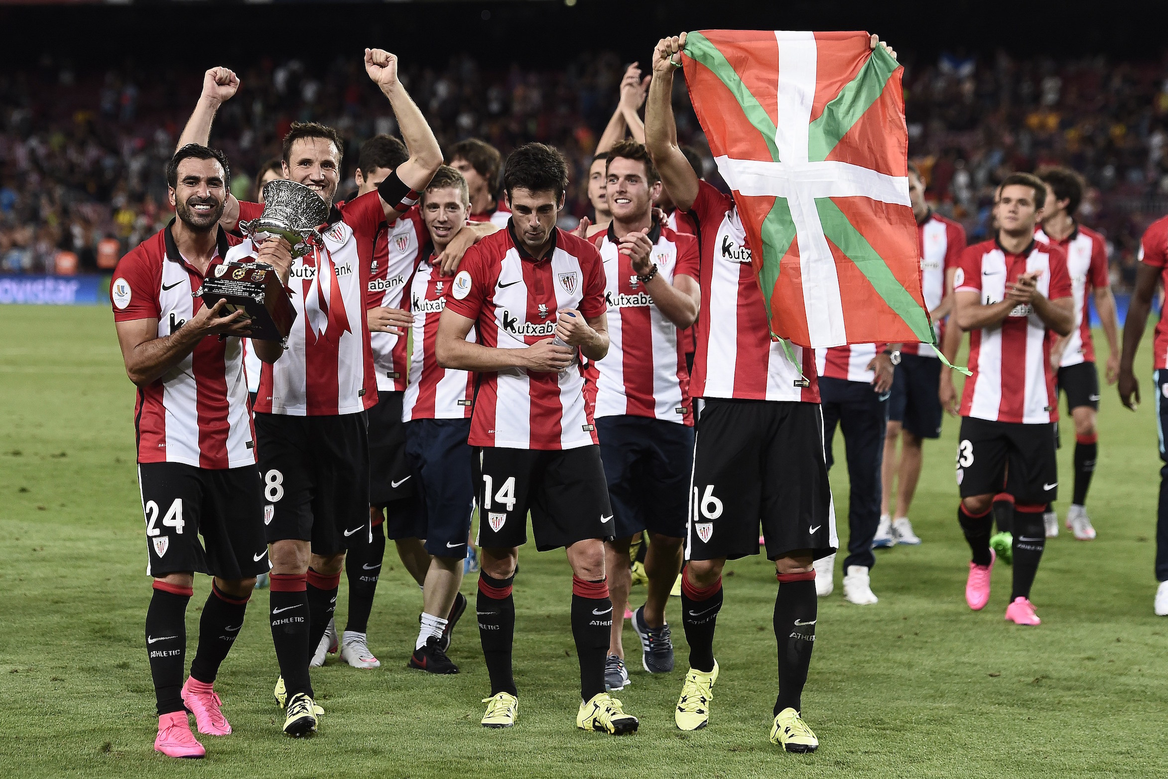 Athletic Bilbao's players wave an ikurrina (Basque flag) and hold their trophy as they celebrate after winning the the Spanish Supercup match during the Spanish Supercup second-leg football match FC Barcelona vs Athletic club Bilbao at the Camp Nou stadium in Barcelona on August 17, 2015. AFP PHOTO / JOSEP LAGO (Photo credit should read JOSEP LAGO/AFP/Getty Images)
