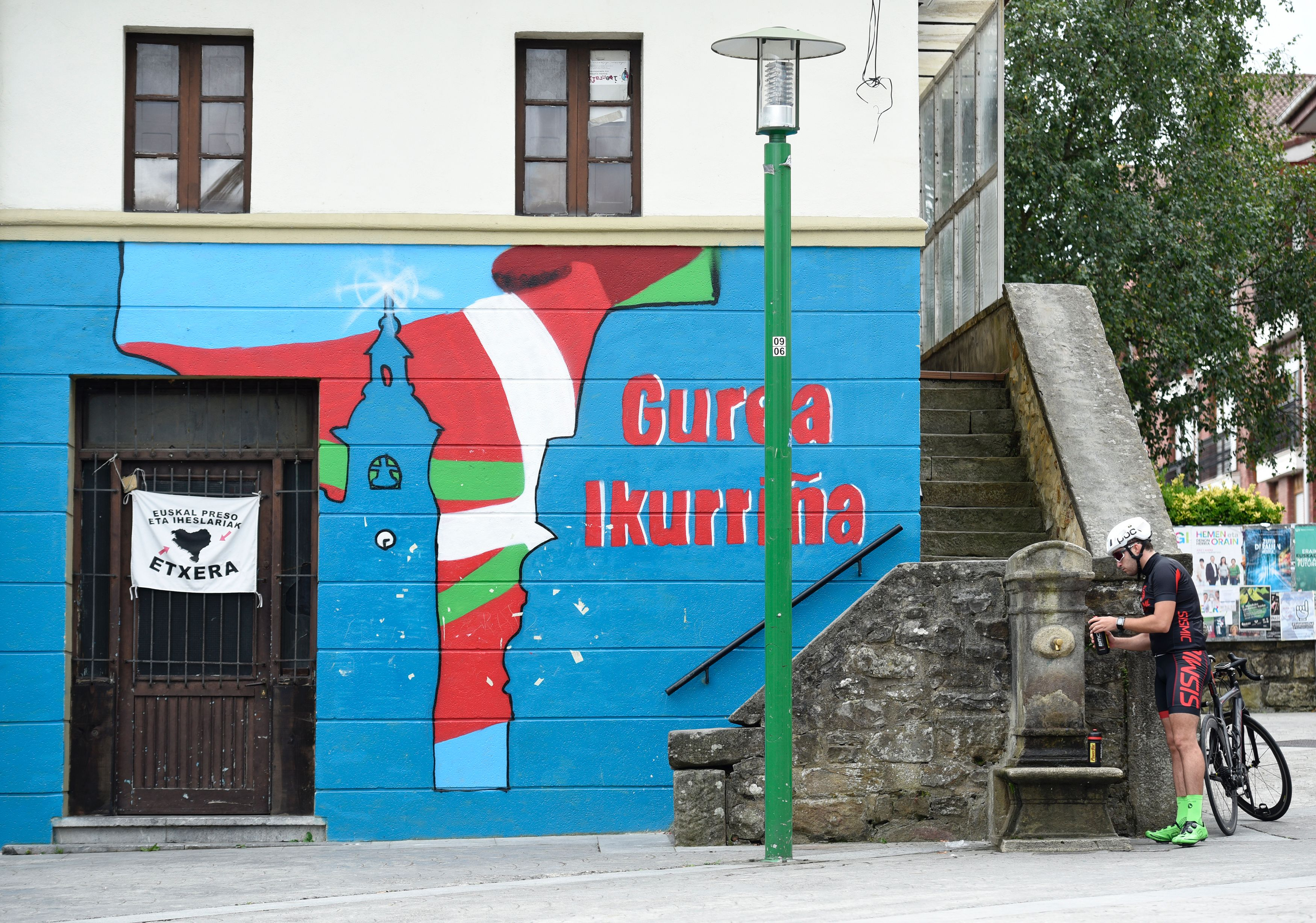 """A cyclist fills a bottle with water of a fountain next to a mural painting reading in Basque """"Ours, is Ikurrina"""" (Basque Country flag) in the main square of the Spanish Basque village of Larrabetzu during the Basque regional elections day on September 25, 2016. Spain's Basque country and Galicia went to the polls today in regional elections that may help unblock the long-lasting national political paralysis. / AFP / ANDER GILLENEA (Photo credit should read ANDER GILLENEA/AFP/Getty Images)"""