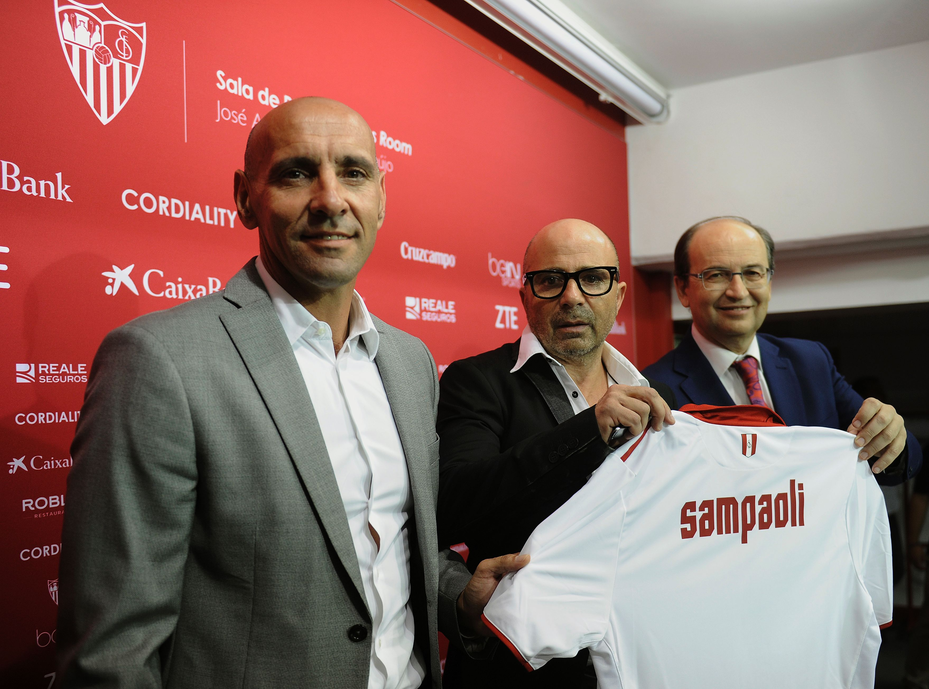 Sevilla's new Argentinian coach Jorge Sampaoli (C) holds a jersey with his name between Sevilla's President Jose Castro (R) and technical director Monchi during his official presentation at the Ramon Sanchez Pizjuan stadium in Sevilla on July 3, 2016. / AFP / CRISTINA QUICLER (Photo credit should read CRISTINA QUICLER/AFP/Getty Images)