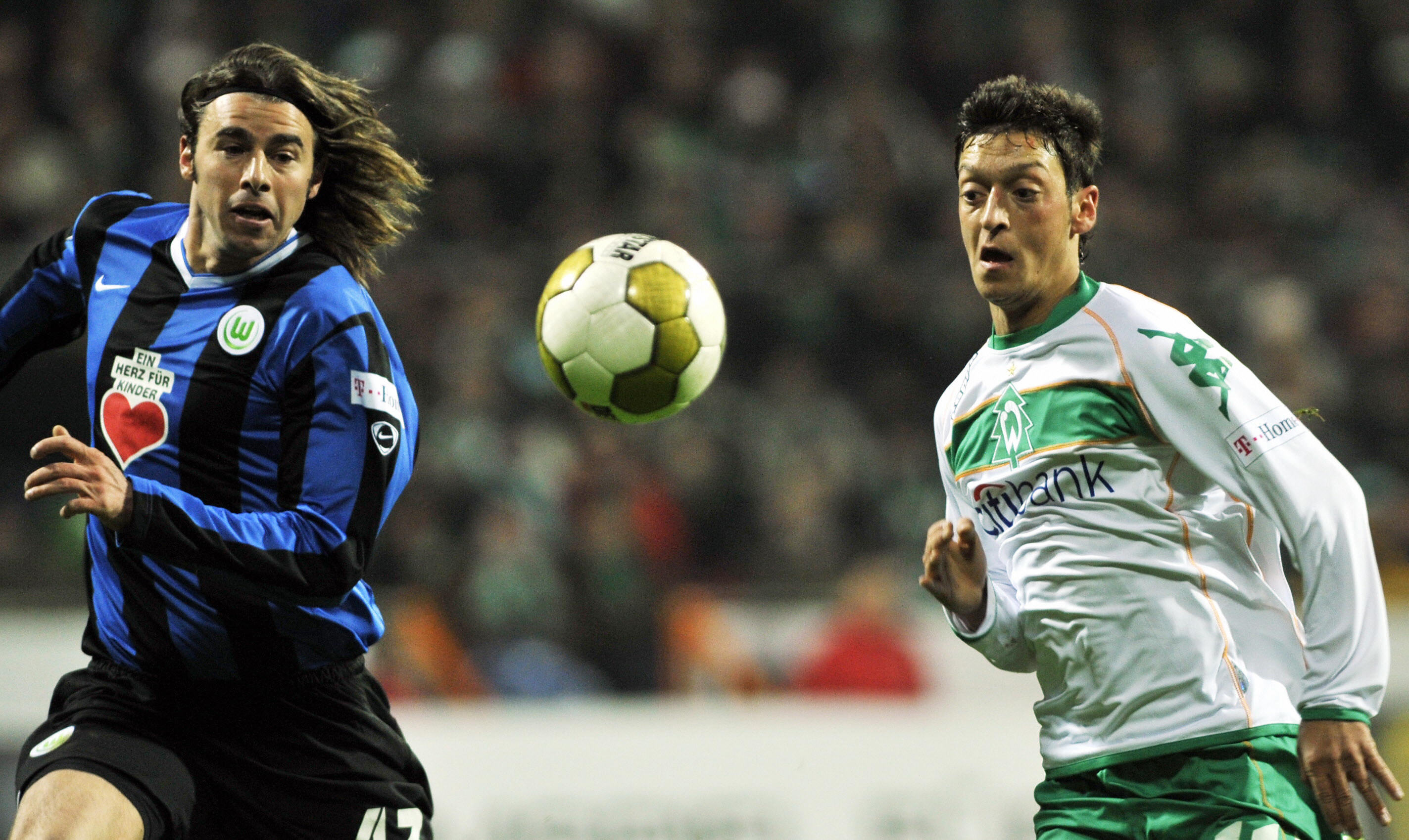 RESTRICTIONS / EMBARGO - ONLINE CLIENTS MAY USE UP TO SIX IMAGES DURING EACH MATCH WITHOUT THE AUTHORISATION OF THE DFL. NO MOBILE USE DURING THE MATCH AND FOR A FURTHER TWO HOURS AFTERWARDS IS PERMITTED WITHOUT THE AUTHORISATION OF THE DFL. Werder Bremen's midfielder Mesut Oezil (R) and Wolfsburg's Italian defender Andrea Barzagli vies for the ball during the German first division Bundesliga football match Werder Bremen vs VfL Wolfsburg in the northern German city of Bremen on December 13, 2008. AFP PHOTO DDP / DAVID HECKER GERMANY OUT (Photo credit should read DAVID HECKER/AFP/Getty Images)