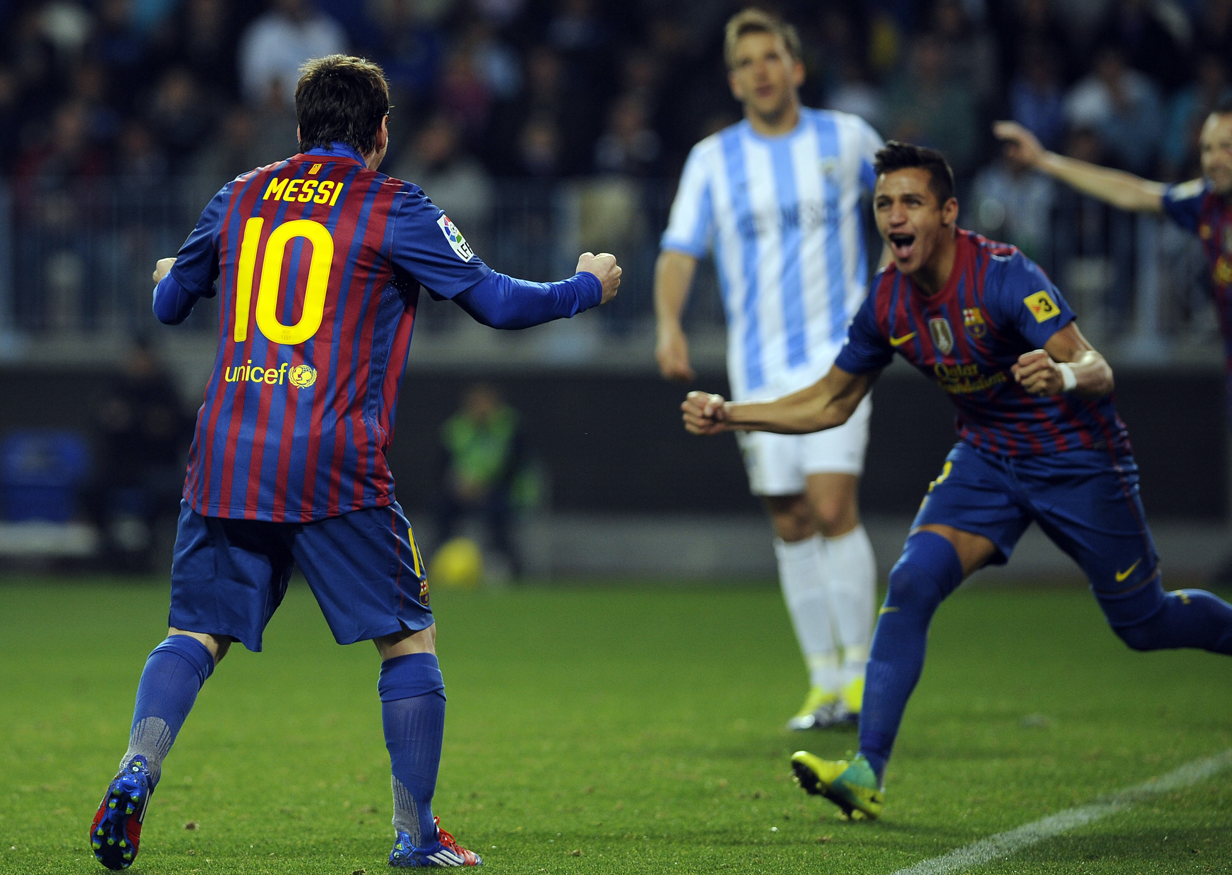 Barcelona's Chiliean forward Alexis Sanchez (R) celebrates with Barcelona's Argentinian forward Lionel Messi (L) after scoring against Malaga during their Spanish League football match, on January 22, 2012 at La Rosaleda stadium in Malaga. Barcelona won 1-4.AFP PHOTO / CRISTINA QUICLER (Photo credit should read CRISTINA QUICLER/AFP/Getty Images)